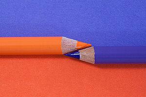 Deux crayons, orange et violet, posés mine contre mine.