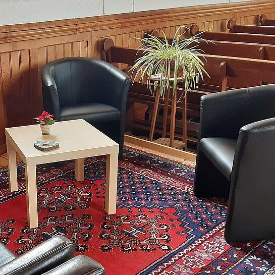 Coin accueil de l'église avec des fauteuils, une petite table, une plante, des jouets...