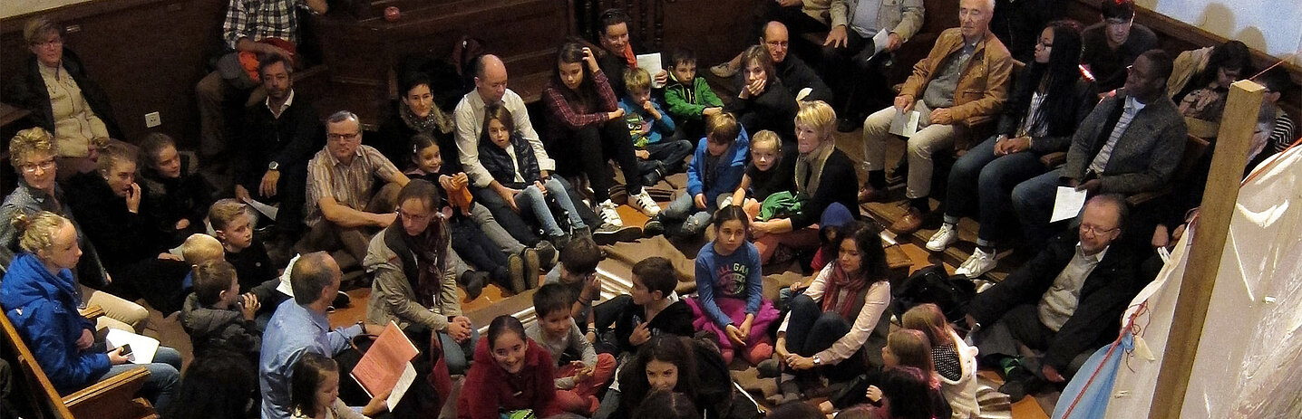 Assemblée réunissant toutes les générations dans une église.