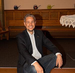 Portrait de Benjamin Corbaz, assis dans une église.