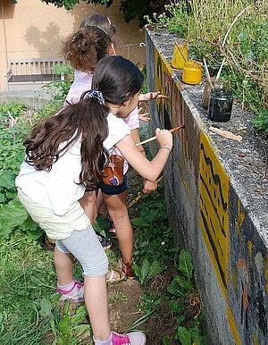 Trois petites filles peignant sur un mur à l'aide de peintures naturelles