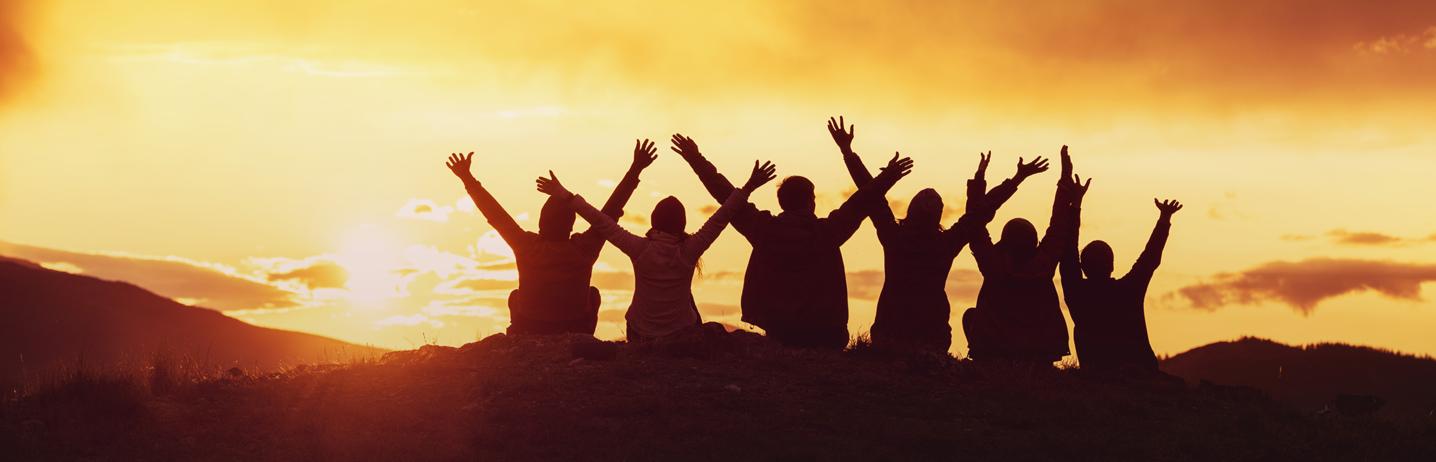 Six jeunes gens tendent les bras vers le ciel avec le soleil couchant.