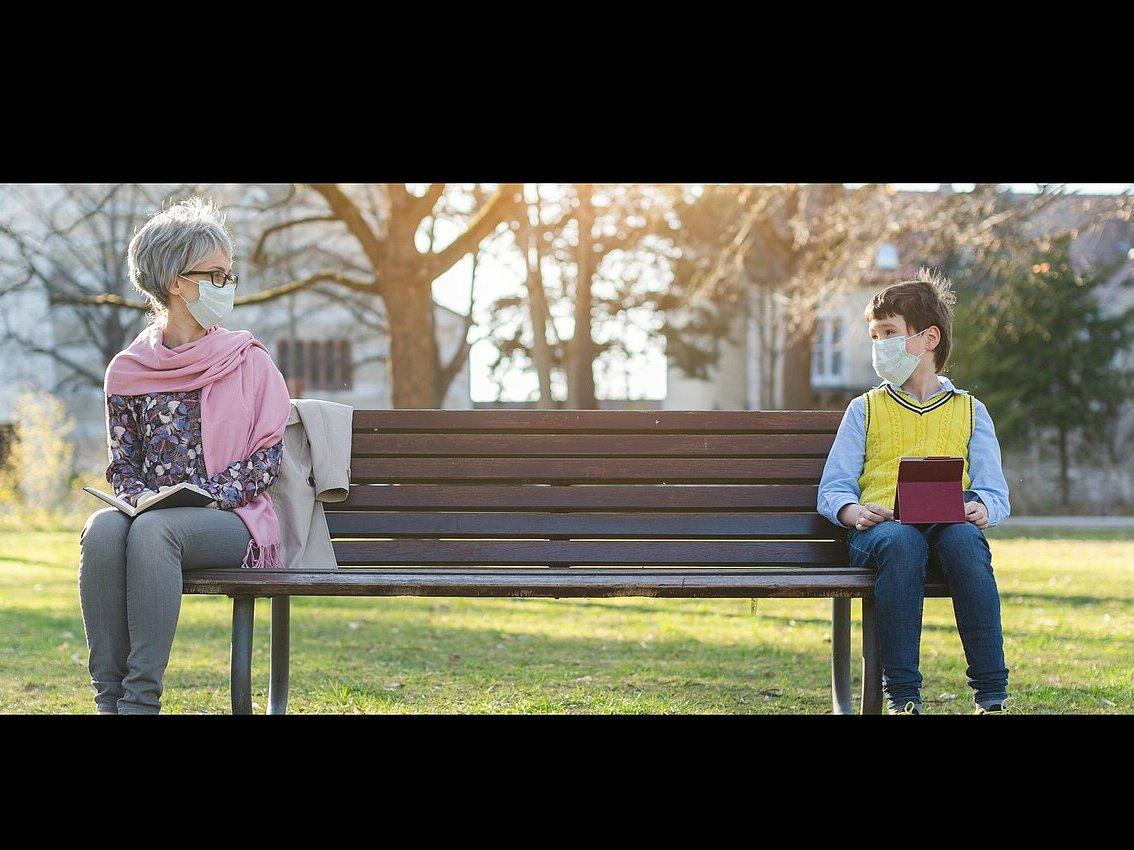 Une personne âgée et un enfant, masqués, sur un banc