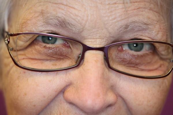 Regard d'une femme âgée porteuse de lunettes.