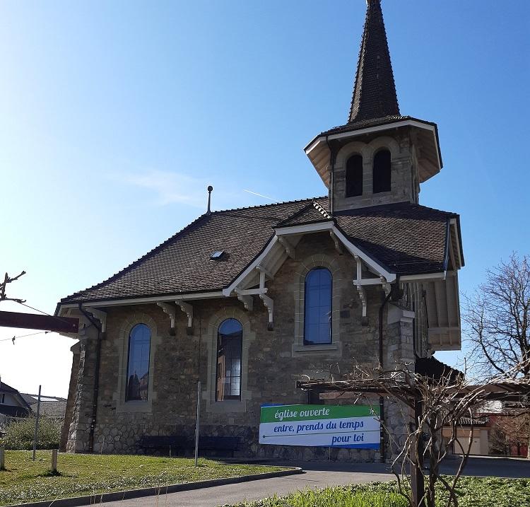 Temple de Chavannes vu depuis son verger, avec une bannière annonçant que l'église est ouverte